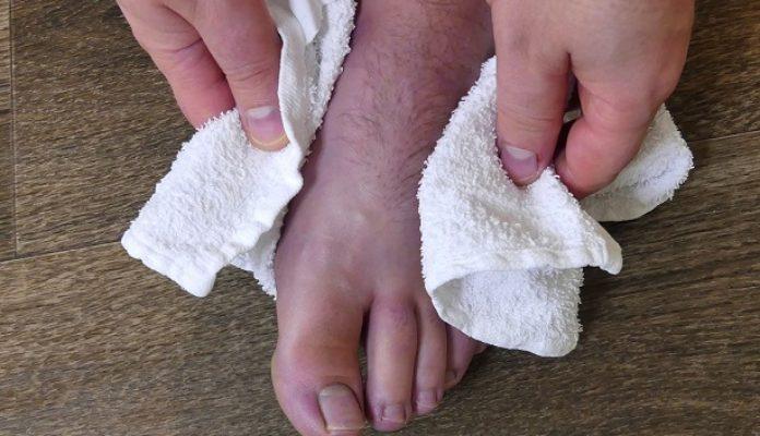 Das gründliche Abtrocknen der Füße ist wichtig während der Nagelpilzbehandlung